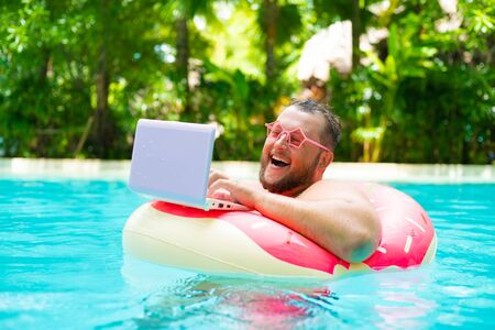 laughing Fat funny man in pink inflatable circle in pink glasses works on a laptop in a swimming pool.