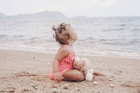 pensive little girl hugging teddy bear and looking away while sitting on seashore Imagens