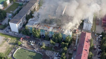 Burning roof of a residential high-rise building, clouds of smoke from the fire. top view.