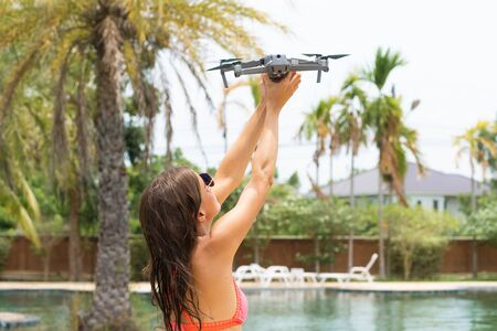 female launches a drone for flight, with which you can take photos and videos, near the swimming pool and palm trees, side view.