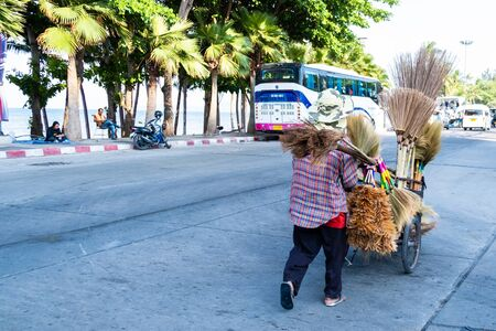 Pattaya, Thailand - May 27, 2019: Unidentified woman sells brooms on a street Stockfoto - 133324799