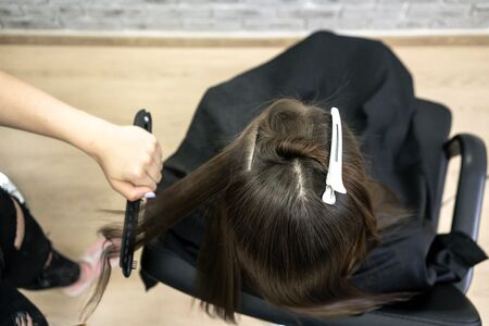 Cute girl with long brunette hair hairdresser doing hair lamination in a beauty salon. concept of hair care treatment, top view.