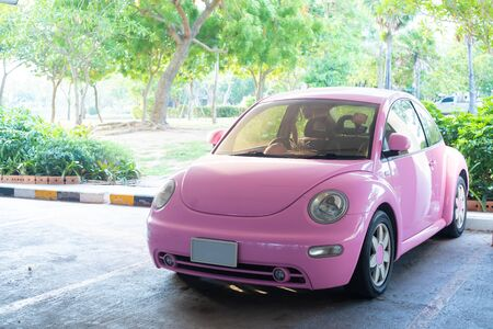 Pattaya, Thailand - May 27, 2019: Modern fun pink small car. Photo of a modern funky pink car parked close to the sea and beach huts