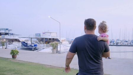Pattaya, Thailand - May 10, 2019: Dad with a small daughter in his arms go to the marina of the yacht berth and consider the yacht, slow motion, 4k Redactioneel