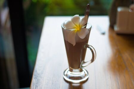 Latte in a glass mug stands on a wooden table with a plumeria flower.