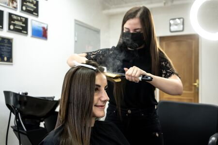 hairdresser makes hair lamination in a beauty salon for a girl with brunette hair. hair care concept Imagens