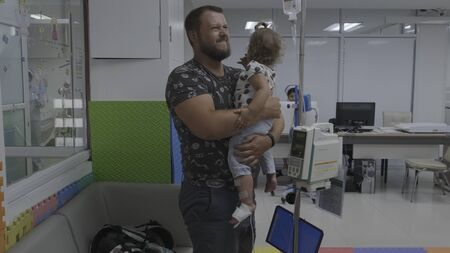 Pattaya, Thailand - May 12, 2019: Surviving sad Dad and crying little daughter in hospital. A little girl is injected. Medical intravenous drip drips, slow motion, 4k