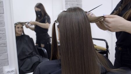 Cute girl with long brunette hair hairdresser doing hair lamination in a beauty salon. concept of hair care treatment. Imagens