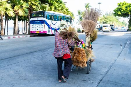 Pattaya, Thailand - May 27, 2019: Unidentified woman sells brooms on a street Stockfoto - 133324859