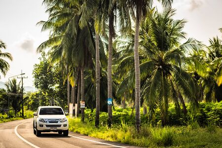 Pattaya, Thailand - May 28, 2019: passing car on a road among palm trees. In clear weather among the jungle and palm trees on a tropical island lies a road.