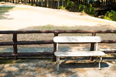 empty white bench near a wooden fence in the garden, in the park, on the street Imagens