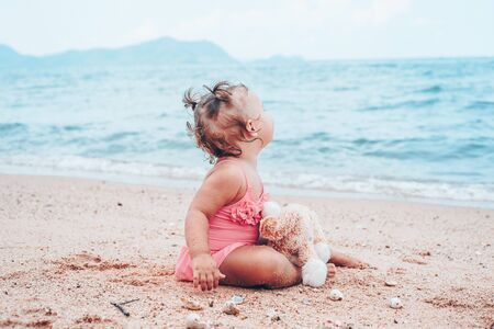 pensive little girl hugging teddy bear and looking away while sitting on seashore Standard-Bild