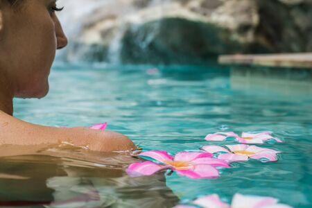 プールで女性。熱帯の花フランジパニプルメリア、水に浮かぶリーラワディー。スパプール。平和と静けさ。スパコンセプト