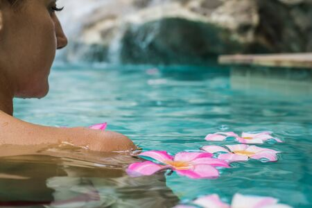 female in a swimming pool. Tropical flowers Frangipani Plumeria, Leelawadee floating in the water. Spa pool. Peace and tranquility. Spa concept