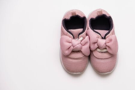 On a white background pink baby female sneakers, copy space. Stockfoto
