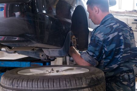 Nizhnevartovsk, Russia - August 12, 2019: Mechanician changing car wheel in auto repair shop