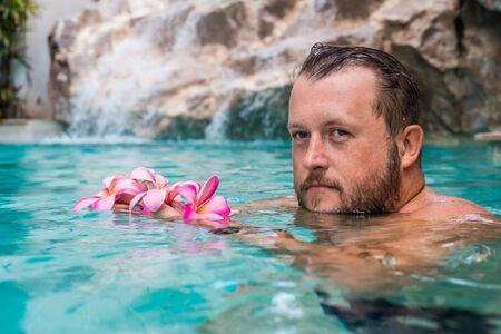 hombre barbudo sostiene flores en la piscina. Flores tropicales Frangipani Plumeria, Leelawadee flotando en el agua. Piscina SPA. Paz y tranquilidad. Concepto de spa