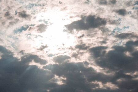 Clouds and the sun shine through the rays of light in the lighted rays. Icturesque sky
