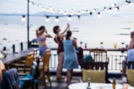 shot of young people toasting drinks at a rooftop party. Blur Abstract Background