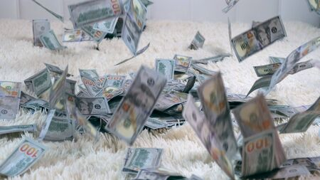 Many banknotes fly in the air on a white bed in slow motion. Huge wealth of money, slow motion, top view. 스톡 콘텐츠