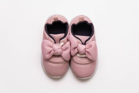 On a white background, pink baby sneakers, copy space. Stockfoto
