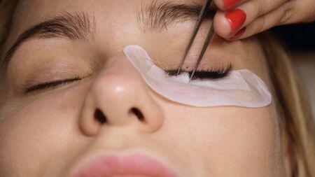 Eyelash extension procedure. The master grows long eyelashes. Female with extended eyelashes.