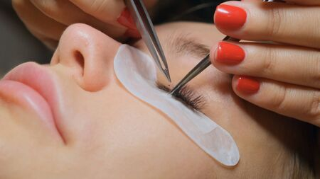 Beautiful Woman with long eyelashes in a beauty salon. Eyelash extension procedure. Lashes close up. Stok Fotoğraf