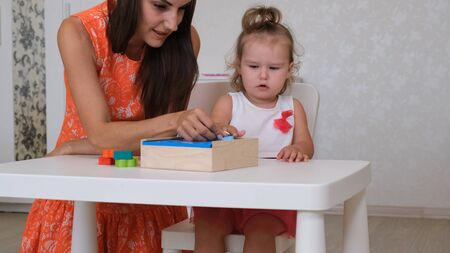 little Daughter with mother, teacher play educational toys, lay and arrange colorful figures. Learning through experience concepts, rough and fine motor skills.