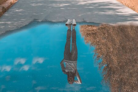 Reflection of a person standing near a puddle. Style is a reflection of your attitude and your personality. The concept of loneliness