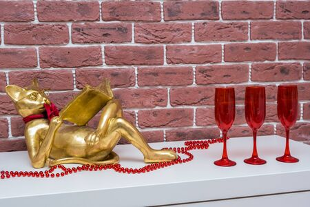 Golden cat reading a book lies on a white surface with red beads and red glasses for wine, living room interior.