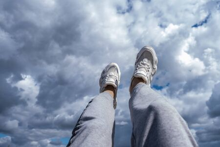 Young man walking in the clouds. Concept, white sneakers on a blue background with clouds.