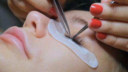 Eyelash Extension Procedure. Woman Eye with Long Eyelashes. Lashes, close up.