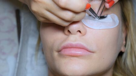 Eyelash removal procedure close up. Beautiful Woman with long lashes in a beauty salon. Eyelash extension