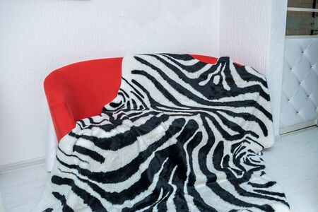 Brightly red sofa with a striped black and white plaid lying on it against a white wall.
