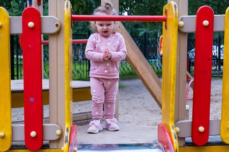 little girl 2 years old plays in the playground on the street. Happy childhood concept.