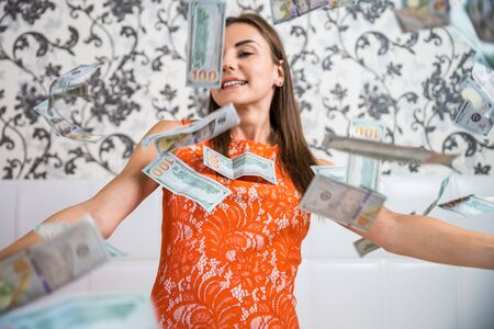 large amount of money falls on a woman white bed. The girl enjoys a lot of money. slow motion. Huge wealth of money, top view.