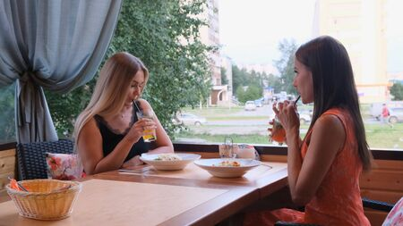 Two long-haired girls are resting in a cafe with a modern interior and laughing. Indoor portrait of funny smiling ladies in fashionable clothes drinking fruit smoothies