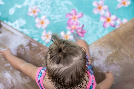 Baby in a swimming pool. Tropical flowers Frangipani Plumeria, Leelawadee floating in the water. Spa pool. Peace and tranquility. Spa concept