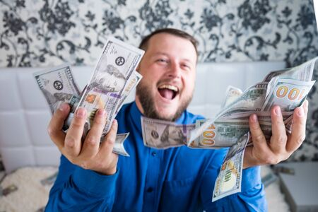 man holds in hands a large amount of money. A man enjoys great wealth, a lot of banknotes of dollars Stock Photo