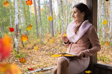 girl in the autumn forest, reads a book, a woman sits near a tree in the autumn forest and holds a book in her hands. Autumn leaves fall in the background.
