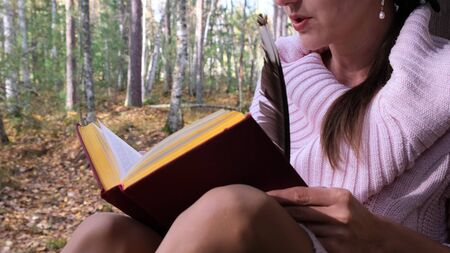 close-up shot of a girl in the autumn forest, a female hand writes with a pen in a book. A woman sits near a tree in the autumn forest and holds a book in her hands..