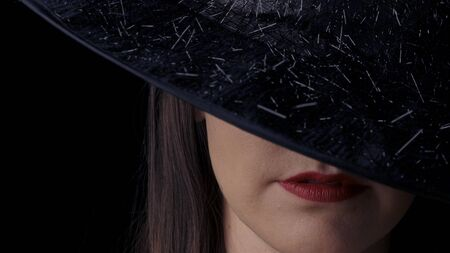 Beautiful sexy woman in a black witch costume with red lips and a hat, looking at the camera and smiling. close-up. Фото со стока
