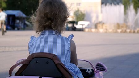 little girl in a blue dress rides a pink baby car in a park. Happy childhood concept. Caricature of an adult woman driving a car Фото со стока