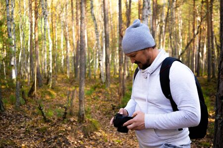 man holds a camera, photographing the autumn nature against the background of a yellowed park 免版税图像