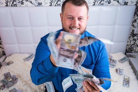 a man in a blue shirt rejoices at the tremendous wealth on the white bed, a lot of money flies in the air Banco de Imagens