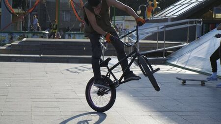 Athletic young guy in a T-shirt doing stunt bike tricks on a city square in the setting sun.