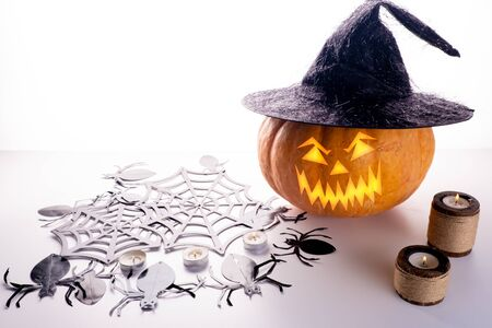 Halloween pumpkin on a white and gray background with candles and foggy smoke. Halloween holiday.