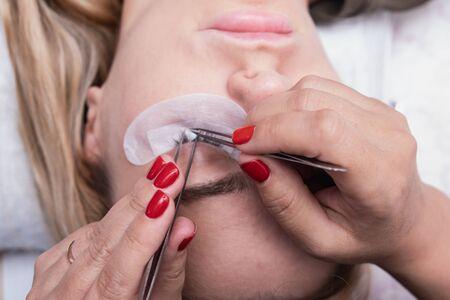eyelash extension master long eyelashes beautiful girl in a beauty salon. Eyelash extension procedure 版權商用圖片 - 132125451