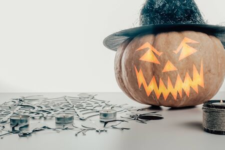 Halloween pumpkin in a witches hat on a white and gray background with candles and foggy smoke. Toned image. Halloween holiday.