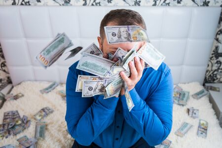 male holds in his hands a lot of money. and kisses them. A man enjoys a lot of cash dollars. Tremendous wealth concept